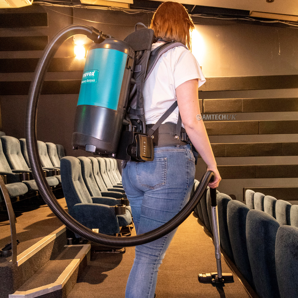 Truvox battery backpack vacuum cleaning carpets in a cinema.