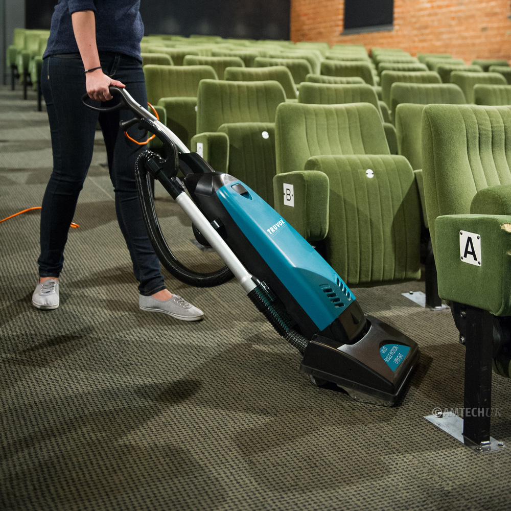 Woman using a Truvox vacuum cleaner in cinema