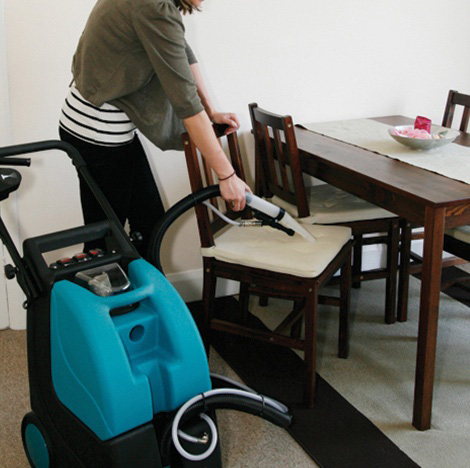 Woman cleaning upholstry with carpet machine